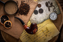 Tobacco Pipe On Old Wooden Background. Vintage Letters, Watches, Coins And Tobacco.