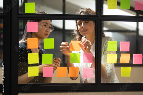 Two multiracial female partners planning business project. Canvas