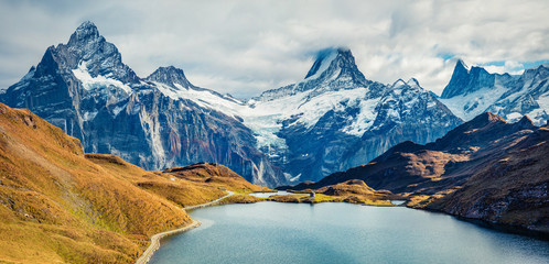 Spectacular morning view of Bachalp lake / Bachalpsee, Switzerland. Wonderful autumn scene of Swiss alps, Grindelwald, Bernese Oberland, Europe. Beauty of nature concept background.