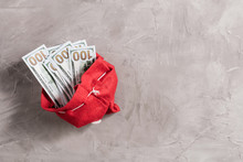 Bundle Of US Dollars In The Funny Santa Claus Red Bag From Felt On The Gray Concrete Background. Cristmas Concept.