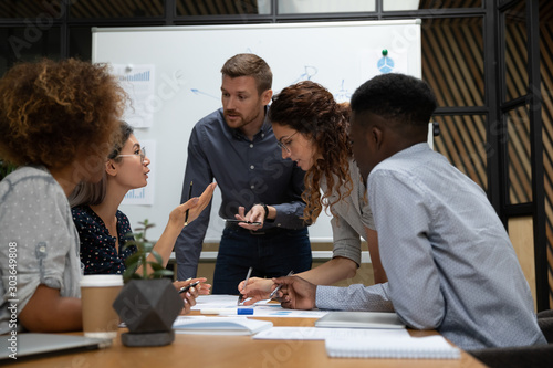 Fotografía Busy millennial group of motivated mixed race teammates discussing project