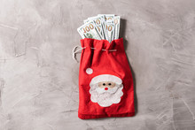 Bundle Of US Hundred Dollars In The Funny Santa Claus Red Bag From Felt On The Gray Concrete Background. Cristmas Concept.