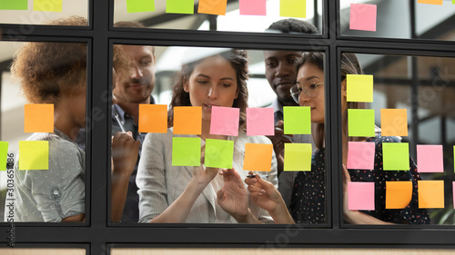 Focused young diverse teammates working with caucasian team leader Canvas Print