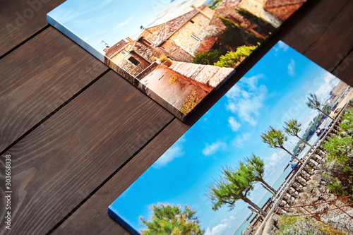 Fototapeta Canvas photo prints lying on a wooden table. Sample of gallery wrapping method of canvas stretching on stretcher bar. Side view of colorful photographs printed on glossy synthetic canvas obraz