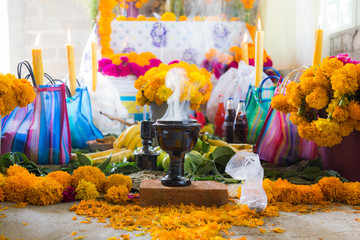 day of the dead, colorful mexican altar and ceramic cup for copal and incense for offerings
