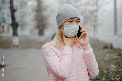 Fototapety, obrazy: A young girl is standing near the road in a medical mask. Protection against a virus epidemic in a city.