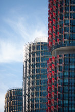 Three Modern Red, Blue And Gray Skyscrapers In A Row At Barangaroo Sydney Australia With A Blue Sky
