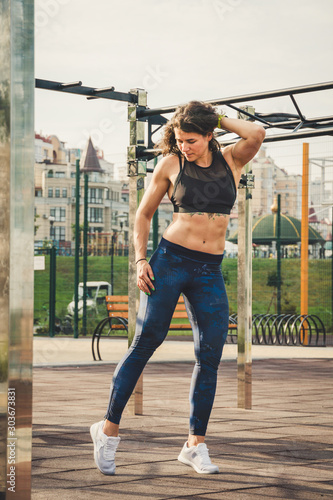 Fototapety, obrazy: Attractive fit young woman in sport wear rest on the street workout area. The healthy lifestyle in the city. Street portrait strong woman poses at gym. Beautiful athletic woman in sports bra posing