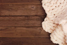 Cozy Knitted Thick Wool Blanket. Top View Side Border On A Rustic Dark Wood Background With Copy Space. Cream Color.