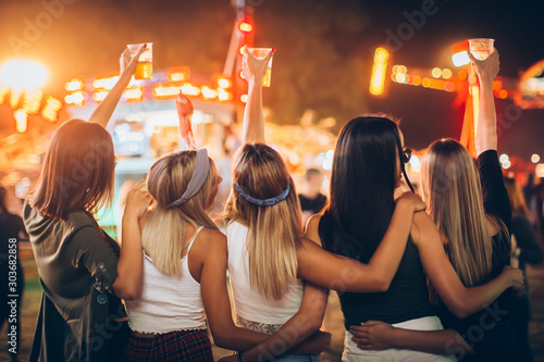Back view of group of girls having fun at the music festival - 303682858
