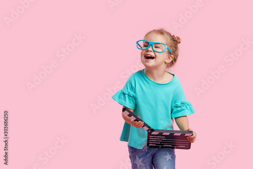 Canvas Funny smiling child girl in cinema glasses hold film making clapperboard isolated on pink background