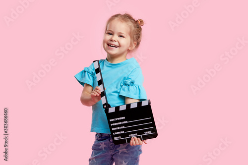 Carta da parati Funny smiling child girl in cinema glasses hold film making clapperboard isolated on pink background