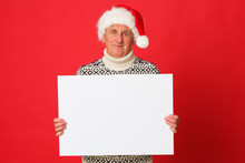 Happy Senior Wearing Santa Claus Hat Is Holding A White Banner.