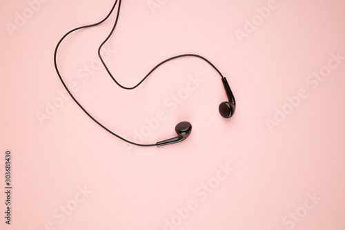 Fotografía  black earphone isolated on a pink pastel backdrop