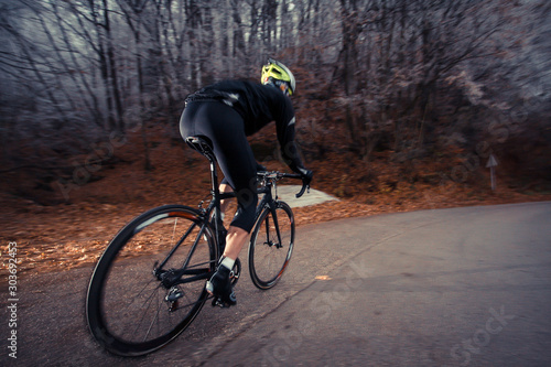 road cyclist in a snowy forest. Cold time for cycling, view of a road cyclist from the back