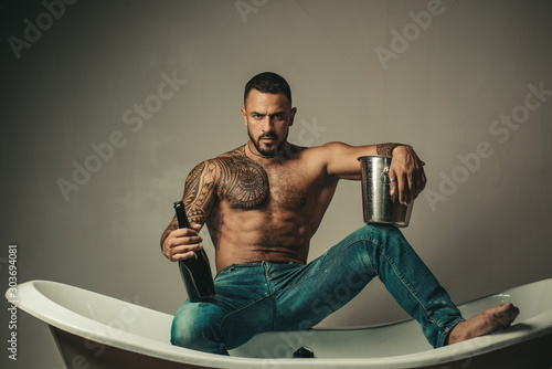 Handsome bearded shirtless man in jeans with sexy body in bathroom. Sexual macho man in bath. Strong muscular tattoed man holding champagne bottle and posing in bathroom. - 303694081