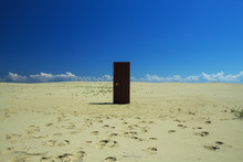 Wooden Door In The Middle Of The Desert, Sand And Clear Sky