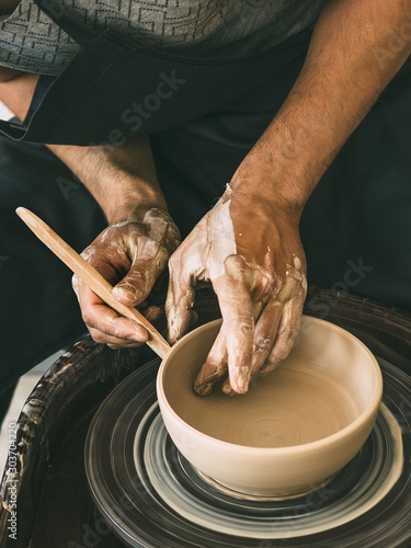Fototapeta Ceramist at a pottery workshop Man is sculpting a bowl behind a rotating potter'