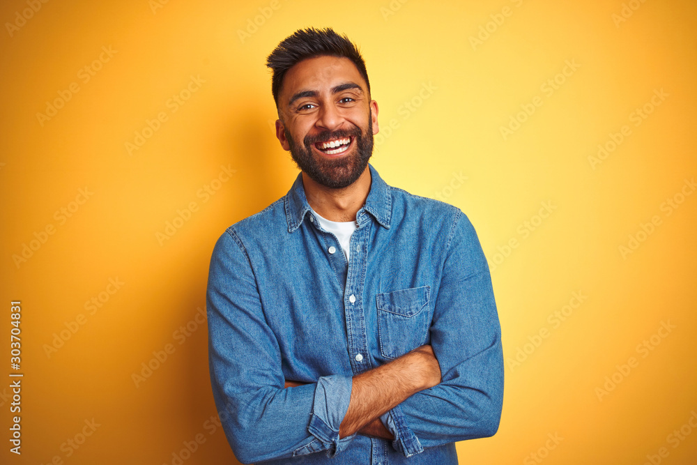 Fototapeta Young indian man wearing denim shirt standing over isolated yellow background happy face smiling with crossed arms looking at the camera. Positive person.