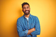 canvas print picture - Young indian man wearing denim shirt standing over isolated yellow background happy face smiling with crossed arms looking at the camera. Positive person.