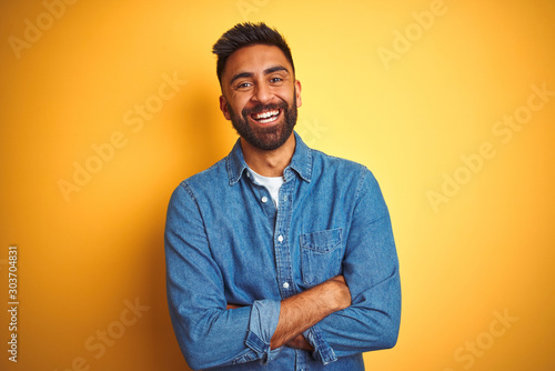 Photo Stands Akt Young indian man wearing denim shirt standing over isolated yellow background happy face smiling with crossed arms looking at the camera. Positive person.