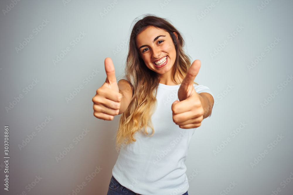 Fototapety, obrazy: Young beautiful woman wearing casual white t-shirt over isolated background success sign doing positive gesture with hand, thumbs up smiling and happy. Cheerful expression and winner gesture.