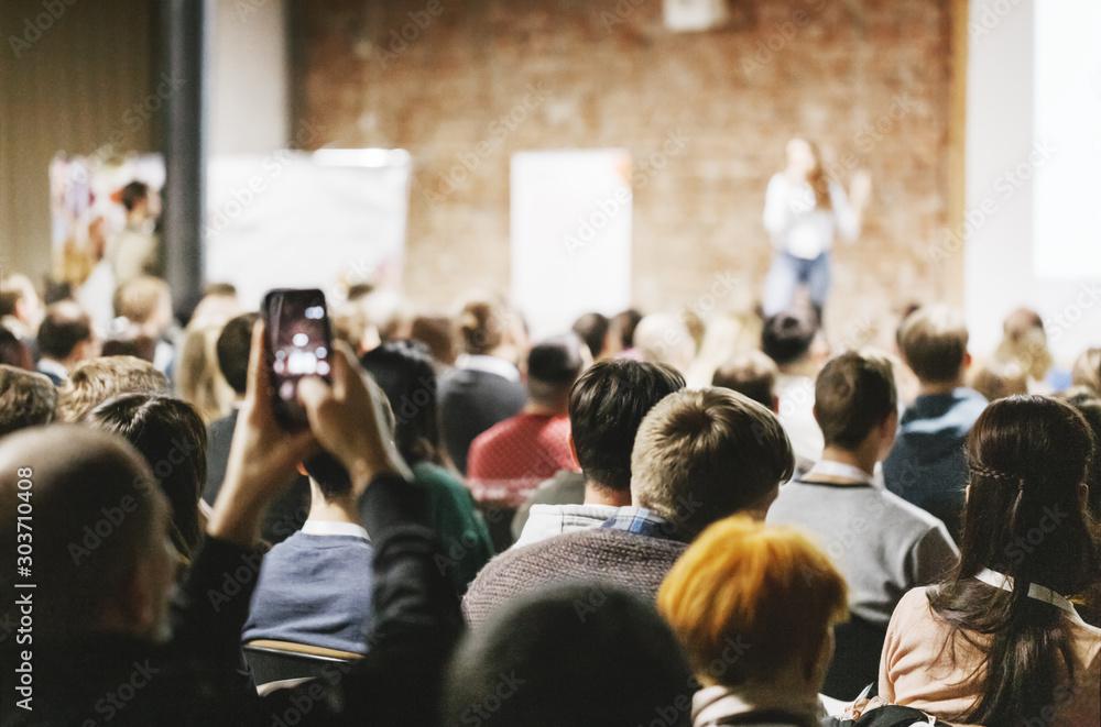 Fototapeta Adult students listen to speaker in auditorium. Rear view.