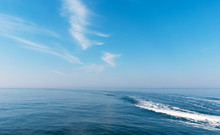 Boat Cruising The Sea Leaving Wake On A Brilliant Sunny Day. Beautiful Blue Sky With Light White Clouds.