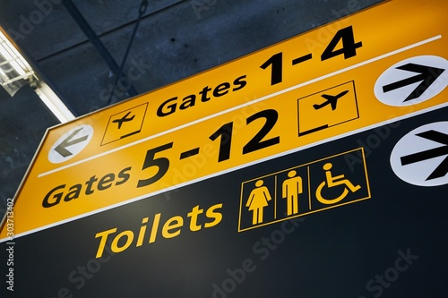 Obraz Toilets and gate signs in an airport terminal - fototapety do salonu