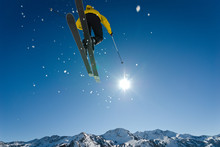 Skier Jumping Through Blue Sky And Sun With Distant Mountains