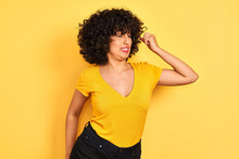 Young Arab Woman With Curly Hair Wearing T-shirt Standing Over Isolated Yellow Background Stretching Back, Tired And Relaxed, Sleepy And Yawning For Early Morning