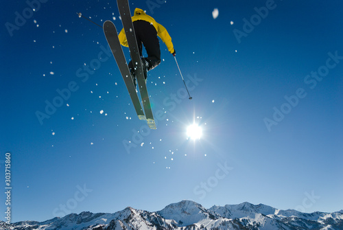 Skier Jumping Through Blue Sky and Sun with Distant Mountains Canvas Print