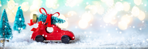 Poster Pays d Europe Toy Wooden Car Carrying Christmas Tree Through Snowy Forest With Bright Soft Bokeh Lights Background - Christmas Concept