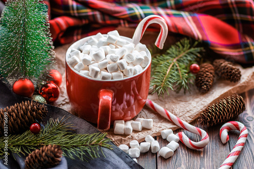 Cappuccino with marshmallow in red mugs and fir-tree branches, striped stick candys, fir cones on wooden table.