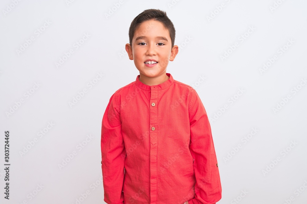 Obraz Beautiful kid boy wearing elegant red shirt standing over isolated white background with a happy and cool smile on face. Lucky person. fototapeta, plakat