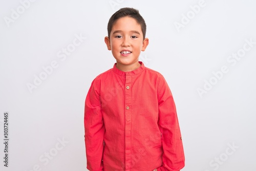 Beautiful kid boy wearing elegant red shirt standing over isolated white background with a happy and cool smile on face. Lucky person.