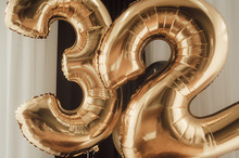 Decor For The Holiday. Gold Foil Balloons, Numbers 32 Against The Background Of Black Curtains, White Tulle