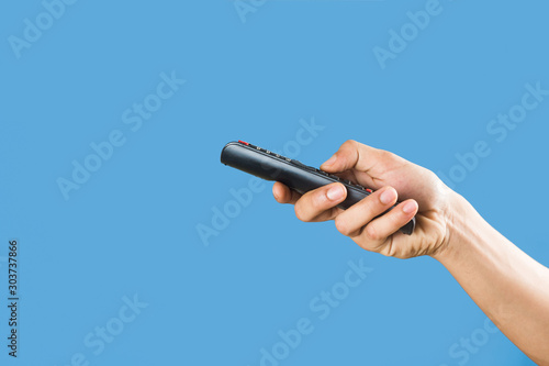 Fotomural  man's hand holding a TV remote control isolated on a light blue background