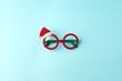 Leinwanddruck Bild - glasses Santa's Christmas on blue background. Masquerade party new year funny sunglasses, trendy minimal winter holiday idea