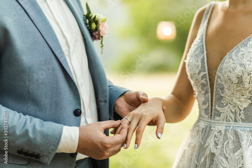 Obraz Man wearing wedding ring on woman hand close up. Symbol of love and commitment. Wedding ceremony vows. - fototapety do salonu