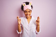 Young african american woman wearing pajama and mask over isolated pink background gesturing finger crossed smiling with hope and eyes closed. Luck and superstitious concept.