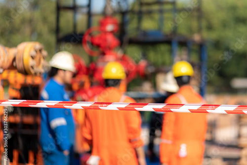 Fototapeta Close up at barricade line which is use to isolate dangerous working area for safety reason with blurred background of working people are conduct safety meeting together