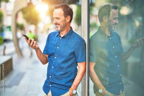 Obraz na plátně  Middle age handsome businessman standing on the street using smartphone smiling
