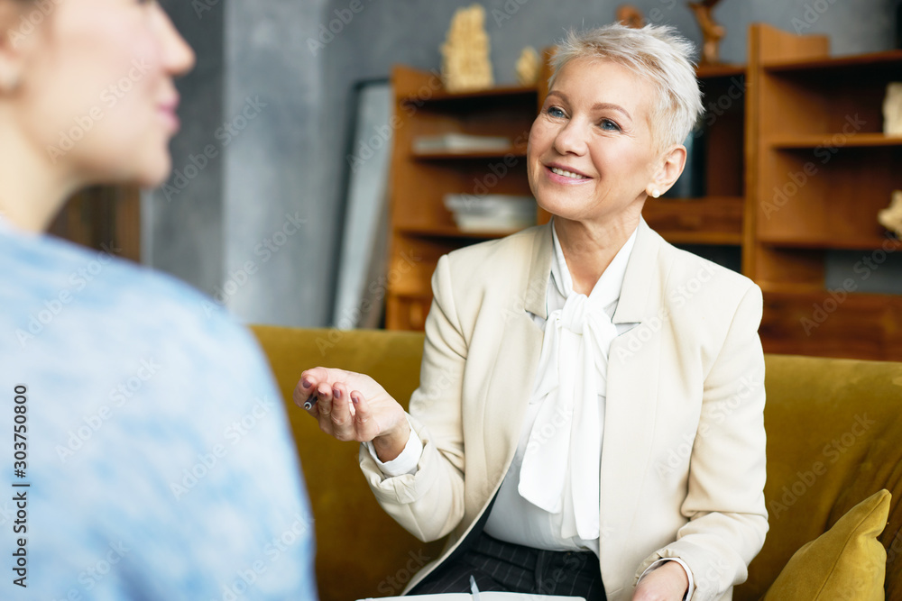 Fototapeta Indoor shot of positive mature female psychologist in elegant suit sitting on couch and making notes while having therapy with unrecognizable woman patient. Psychological support and counseling