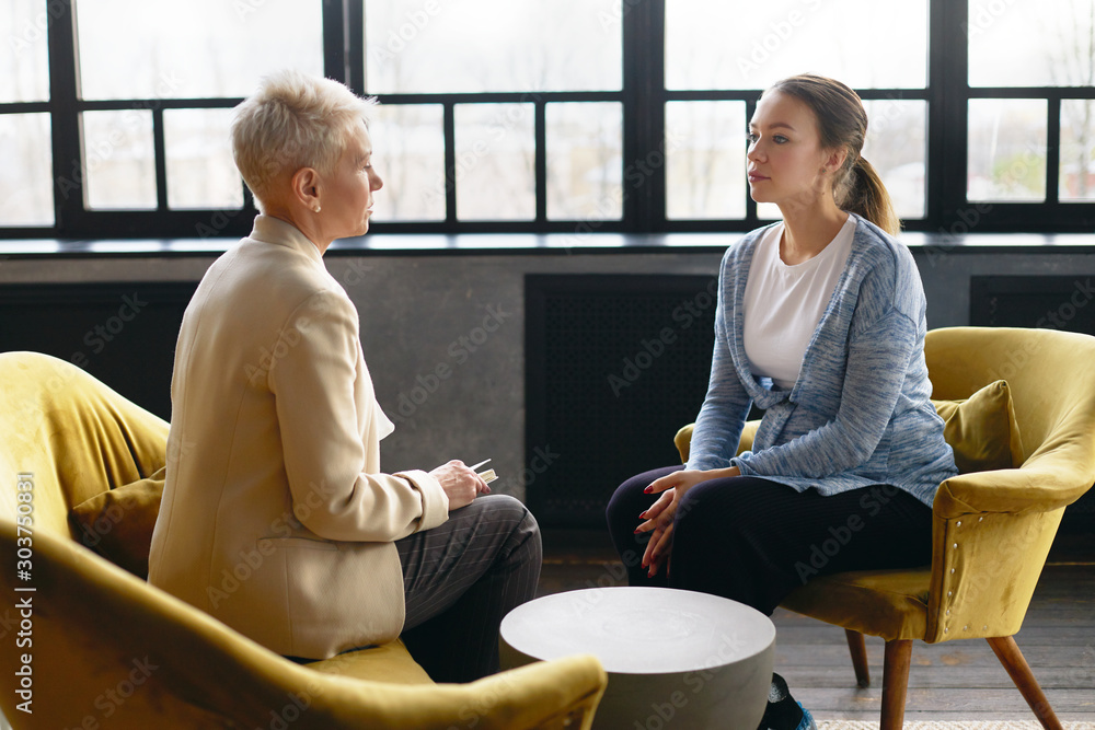 Fototapety, obrazy: Side view image of two women sitting face to face in comfortable armchairs. Stylish mature female psychotherapist conducting counselling with young pregnant woman. Job interview and human resources