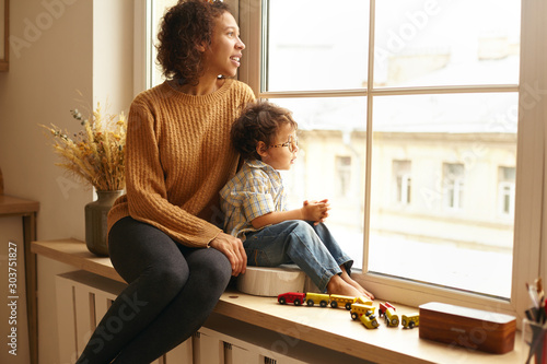 Obraz Cozy scene of joyful young Latin female wearing jeans and knitted jumper sitting on windowsill hugging her cute chubby little child, both watching outside, talking, having dreamy thoughtful expression - fototapety do salonu