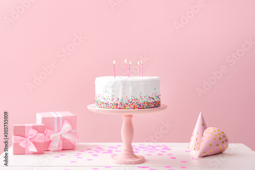 Valokuva Tasty Birthday cake with gifts on table against color background