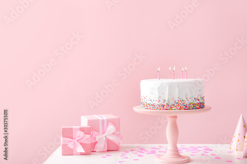 Obraz na plátne Tasty Birthday cake with gifts on table against color background