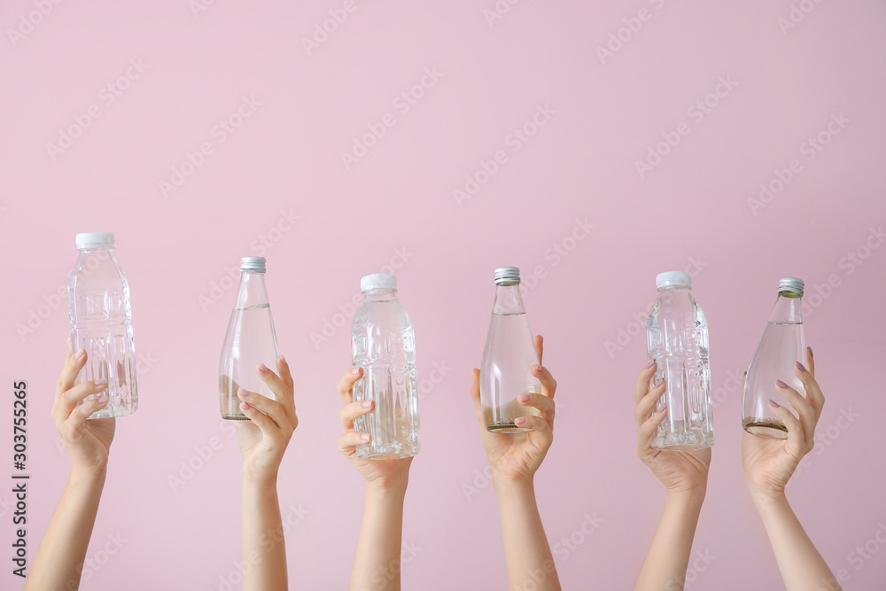 Fototapety, obrazy: Female hands with bottles of water on color background