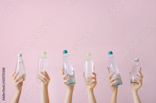 Carta da parati  Female hands with bottles of water on color background
